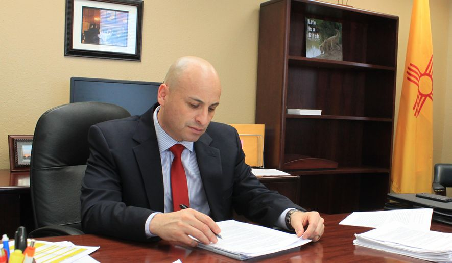 New Mexico Attorney General Hector Balderas reviews documents related to a lawsuit against one of the nation's largest nursing home chains in his office in Albuquerque N.M., on Tuesday, March 31, 2015. Balderas said he decided to pursue the lawsuit following a months' long review of the merits of the case to ensure it was in the best interest of New Mexicans. (AP Photo/Susan Montoya Bryan)