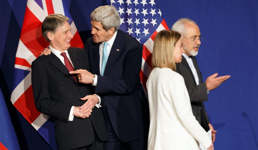 Negotiators: Secretary of State John F. Kerry grabbed British Foreign Secretary Philip Hammond for a chat before a press conference Thursday announcing a long-awaited framework for Iranian nuclear activity. Also attending were Federica Mogherini of the European Union and Iranian Foreign Minister Mohammad Javad Zarif. (Associated Press)