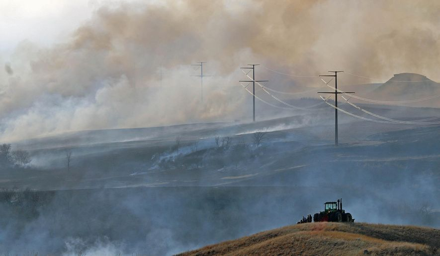 Three ranch hands watch from a hillside as a wind-driven grass fire sweeps across the hills on the Price Ranch north of Mandan, N.D., Tuesday, March 31, 2015. (AP Photo/The Bismarck Tribune, Tom Stromme)