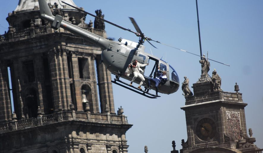 "Stunt doubles perform an action scene aboard a helicopter above the Zocalo, Mexico City's main square during the filming of ""Spectre,"" the latest of the James Bond 007 movies, in Mexico, Monday, March 30, 2015. The latest installment of the 007 movie franchise began filming in Mexico City this March. (AP Photo/Sandra Stargardter)"