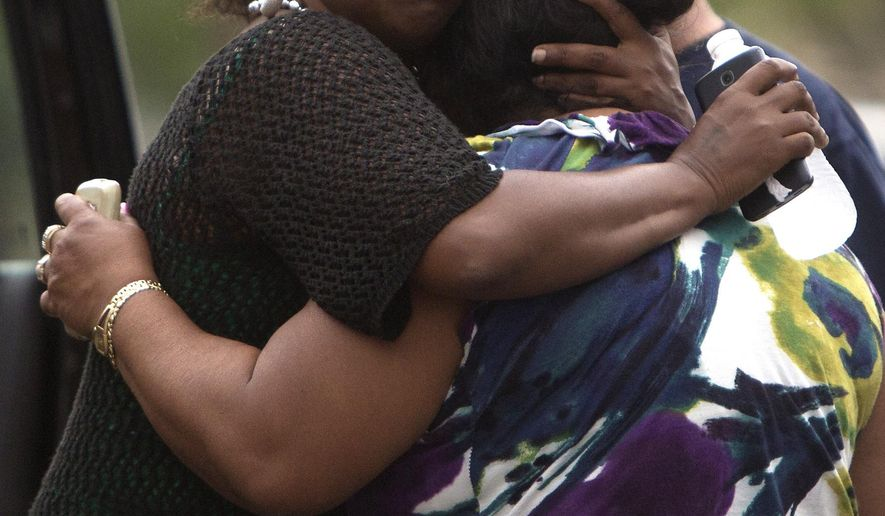 Family members console each other at the scene after a woman was found dead in an apartment in the 1900 block of Runnels, Thursday, April 2, 2015, in Houston. Houston police say a woman has been shot to death in her apartment where her five young children were later found unharmed. (AP Photo/Houston Chronicle, Cody Duty)