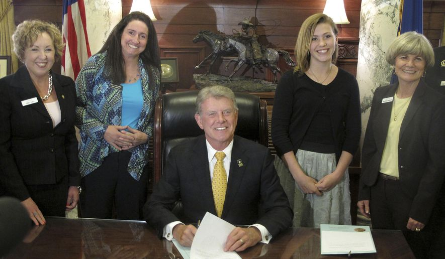 "Gov. C.L. ""Butch"" Otter, center, poses for a picture with Ilah Hickman, second from right, and other state lawmakers while signing law allowing the Idaho giant salamander to be Idaho's official state amphibian in Boise, Idaho on Thursday, April 2, 2015. Hickman lobbied the Idaho Legislature to pass her law for nearly five years before winning enough support in both chambers. (AP Photo/Ryan Struyk)"