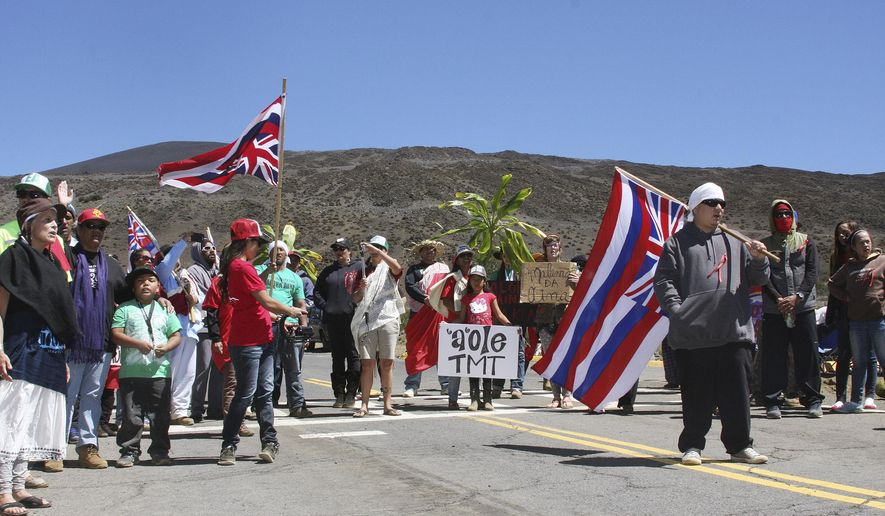 FILE - In this March 30, 2015, file photo, protesters form a road block outside the Mauna Kea visitors center in Hilo, Hawaii. Protesters on Hawaii's Big Island have been blocking the road to a mountain peak where one of the world's largest telescopes is being built. Hawaii County police spokeswoman Chris Loos said Thursday, April 2, 2015, that some people have been arrested for blocking the road to the Mauna Kea summit, which is held sacred by Native Hawaiians. (AP Photo/Hawaii Tribune Herald, Tom Callis, File)