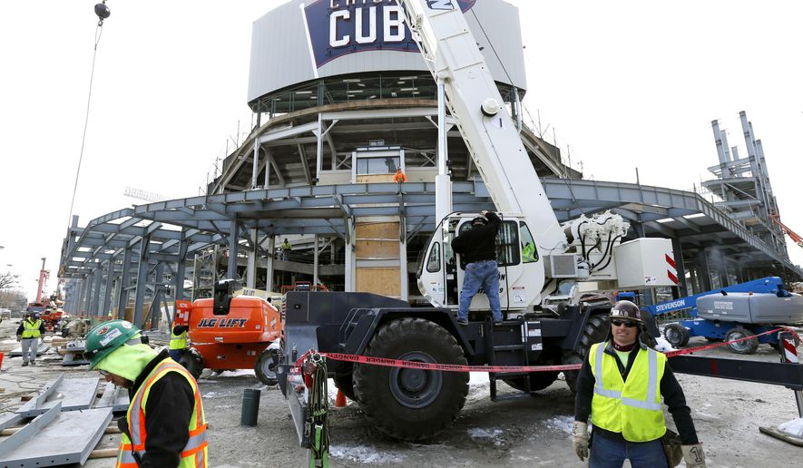 In this Tuesday, March 24, 2015, photo, construction continues on renovations around Wrigley Field's center field in Chicago. When fans arrive for the Chicago Cubs' baseball season opener Sunday, April 5, 2015, against the archrival St. Louis Cardinals, they will get their first real look at the most visible phase of a massive renovation project. Just like in 1937, there will be new bleachers and a new brick outfield wall, just recently adorned with ivy. Even the centerpiece of the project, a brand new Jumbotron, will harken back to the day when Depression-era fans beheld a state-of-the-art manual scoreboard. (AP Photo/Charles Rex Arbogast)