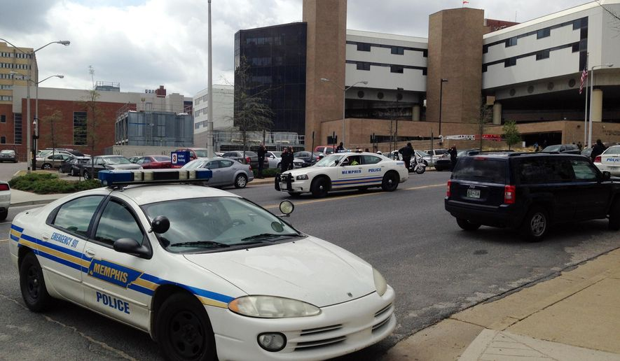 Memphis police block the street in front of a hospital Thursday, April 2, 2015, in Memphis, Tenn., where an officer who was shot was taken to. Memphis police spokeswoman Alyssa Macon-Moore said the officer is in critical condition and that a suspect is in custody. (AP Photo/Adrian Sainz)