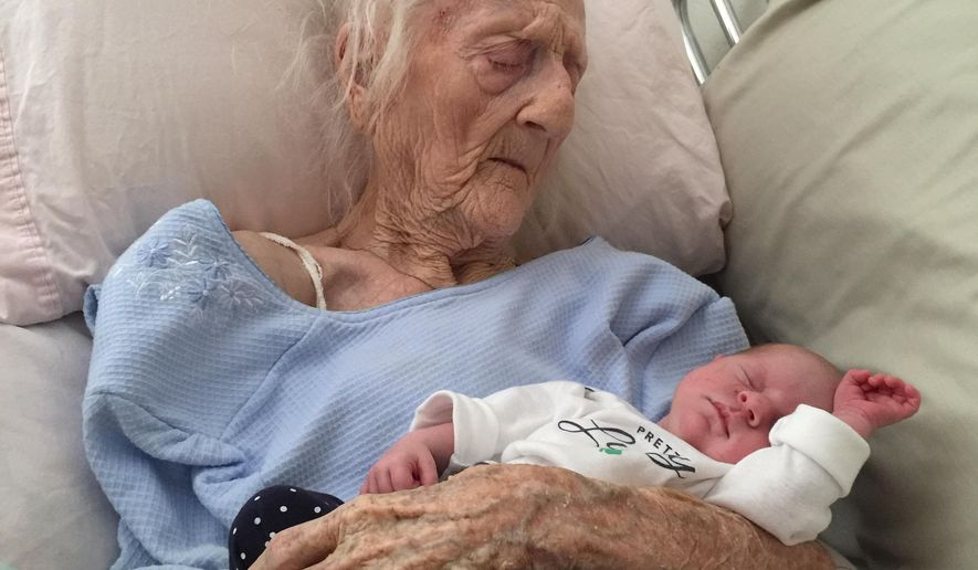 In this photo provided by Sarah Hamm, Rosa Camfield holds her newborn great-granddaughter, Kaylee, in Chandler, Ariz., on March 17, 2015. Camfield, 101, died in her sleep late Monday night, March 30, 2015. She became a social media sensation earlier this month thanks to a Facebook posting of the photo. (AP Photo/Courtesy of Sarah Hamm)