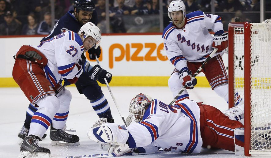 New York Rangers goaltender Henrik Lundqvist (30) stretches out for the puck as Winnipeg Jets Dustin Byfuglien (33) looks for the rebound and Rangers' Ryan McDonagh (27) and Dan Girardi (5) defend during the second period of an NHL hockey game Tuesday, March 31, 2015, in Winnipeg, Manitoba. (AP Photo/The Canadian Press, John Woods)
