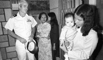 U.S. Navy Commander John S. McCain 3rd, a guest of the South Vietnamese government, visits the Holt orphanage in Saigon, Vietnam, on Oct. 30, 1974.  The institution cares for many youngsters fathered by American G.I.s.  McCain, son of the admiral who commanded U.S. forces in the Pacific at the height of the Vietnam War, was shot down over Hanoi and spent several years as a POW.  (AP Photo/Dang Van Phuoc)