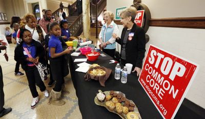 Schoolchildren from Meridian, Miss., file past Opponents of Common Core table in the Mississippi State Capitol in Jackson. (AP Photo/Rogelio V. Solis)