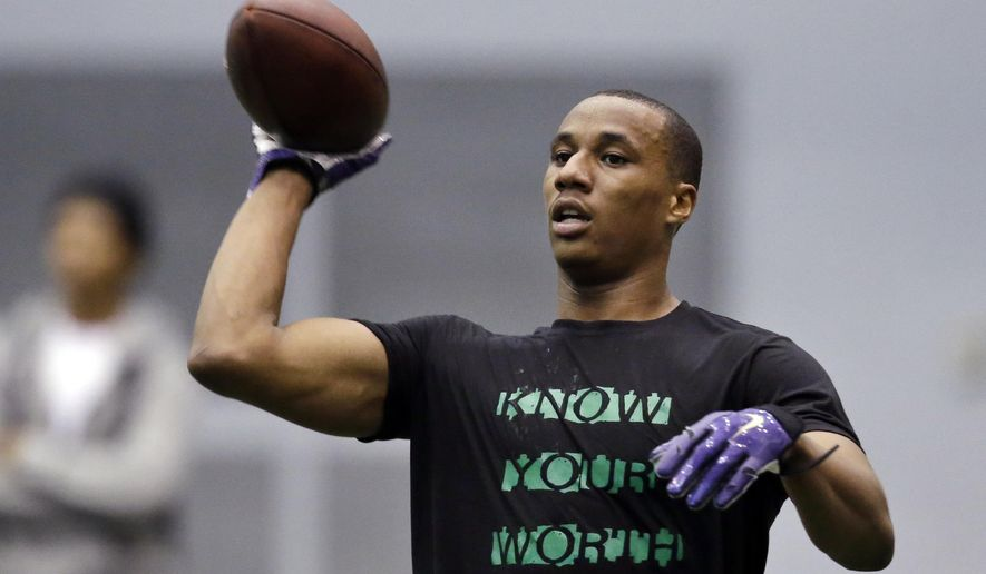 Former Washington player Marcus Peters tosses back a ball as he works out at Washington's pro day Thursday, April 2, 2015, in Seattle. Potential first-round picks Danny Shelton and Shaq Thompson were among about 20 former Washington players who worked out for NFL officials and others. (AP Photo/Elaine Thompson)