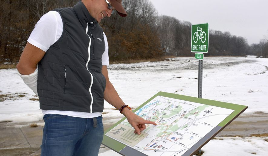 In this March 9, 2015 photo, Frank Brummer, board president of Trail Recreation Effingham County (TREC), points out the proposed location of the Brumleve Nature Center on a map of the trail system, located at the Hilltop Estates trailhead near Effingham, Ill. TREC plans to develop the nature center in honor of Joe and Suzette Brumleve, who died in a plane crash three days before Christmas 2008.  Brummer said the tentative plan is to develop some unpaved trails around the tract with interpretive signage. (AP Photo/Effingham Daily News, Bill Grimes)