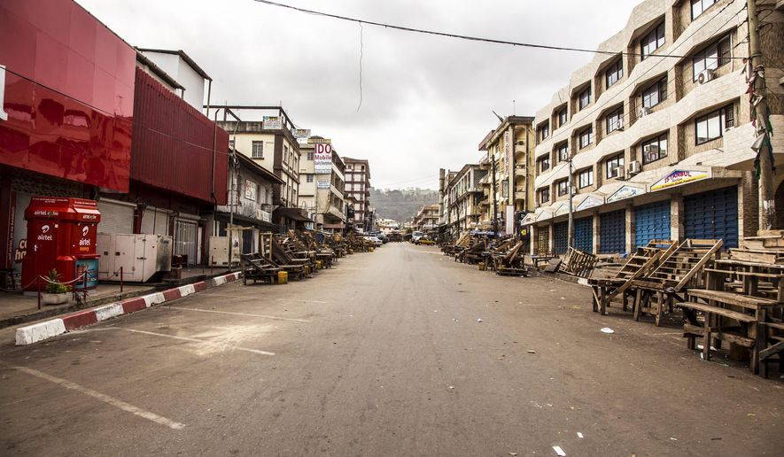 FILE - In this file photo dated Friday, March. 27,  2015, a usually busy street is deserted as Sierra Leone enters a three day country wide lockdown on movement of people due to the Ebola virus in the city of Freetown, Sierra Leone. Sierra Leone's 6 million people were told to stay home for three days, except for religious services, beginning Friday as the West African nation attempted a final push to rid itself of Ebola. (AP Photo/ Michael Duff, FILE)
