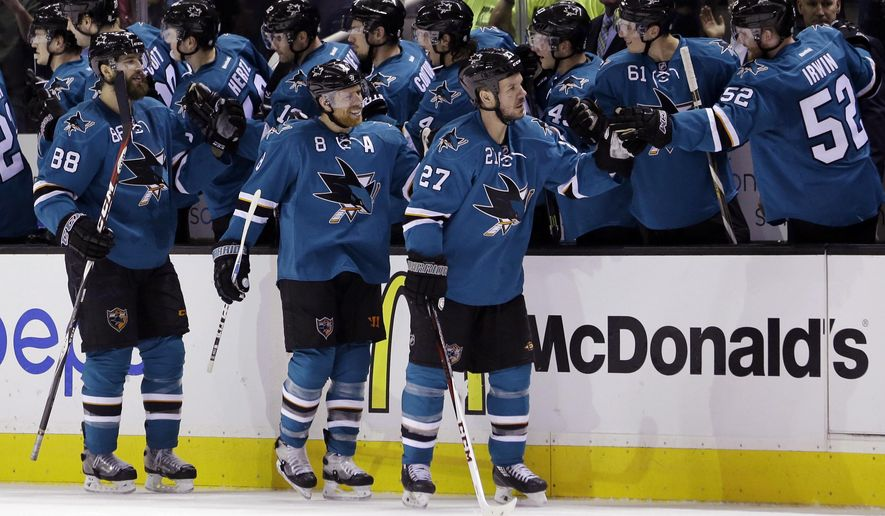 San Jose Sharks' Scott Hannan (27) celebrates his goal with teammates on the bench alongside, teammates Joe Pavelski (8) and Brent Burns (88) during the second period of an NHL hockey game against the Colorado Avalanche Wednesday, April 1, 2015, in San Jose, Calif. (AP Photo/Marcio Jose Sanchez)