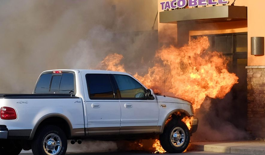 In this photo taken Wednesday, April 1, 2015, a pickup truck caught fire outside the doors of Taco Bell in Mason City, Iowa. The restaurant was evacuated. No one was injured.  (AP Photo/The Globe Gazette, Arian Schuessler)