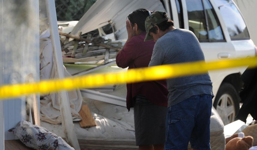 Family members grieve as they look at what is left of a room where Ivan Carlos and Brenda Aviliz were sleeping Wednesday morning, April 1, 2015, when an SUV veered from U.S. 41 striking their mobile home in Palmetto, Fla.'s Lone Oak Park, killing the couple and their unborn baby. Police say the 35-year-old driver was taken to a hospital with injuries not considered life-threatening. (AP Photo/The Bradenton Herald, Grant Jefferies)