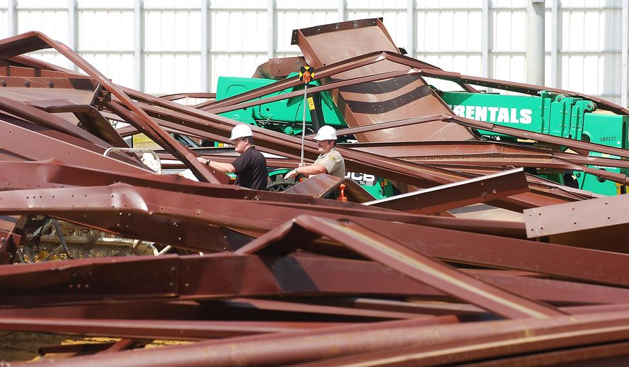Investigators go through the twisted metal at the scene of the building collapse at Argyle High School Thursday. April 2, 2015, in Argyle, Texas. One worker has been killed and three hurt when the steel frame of an under-construction activities center collapsed outside the North Texas school. (AP Photo/The Dallas Morning News, Al Key)  MANDATORY CREDIT; MAGS OUT; TV OUT; INTERNET USE BY AP MEMBERS ONLY; NO SALES