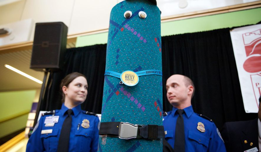 TSA officers Andrea Green, left,  and Edmund Gray stand beside a piece of dressed up old carpet from the terminal at Portland International Airport during a press conference in Portland Ore., March 20, 2015.  After enduring three decades of luggage wheels and travel-worn passengers, the teal-color carpet is being replaced and as word spread that the carpet was going to be torn up it became an online and marketing superstar. (AP Photo/The Oregonian, Michael Lloyd)
