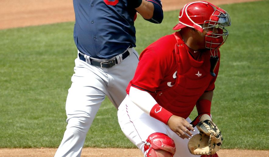 Cleveland Indians' Michael Brantley scores on an RBI double by teammate Roberto Perez as Cincinnati Reds catcher Brayan Pena waits for the throw during the fourth inning of a spring training baseball game, Thursday, April 2, 2015, in Goodyear, Ariz. (AP Photo/Matt York)