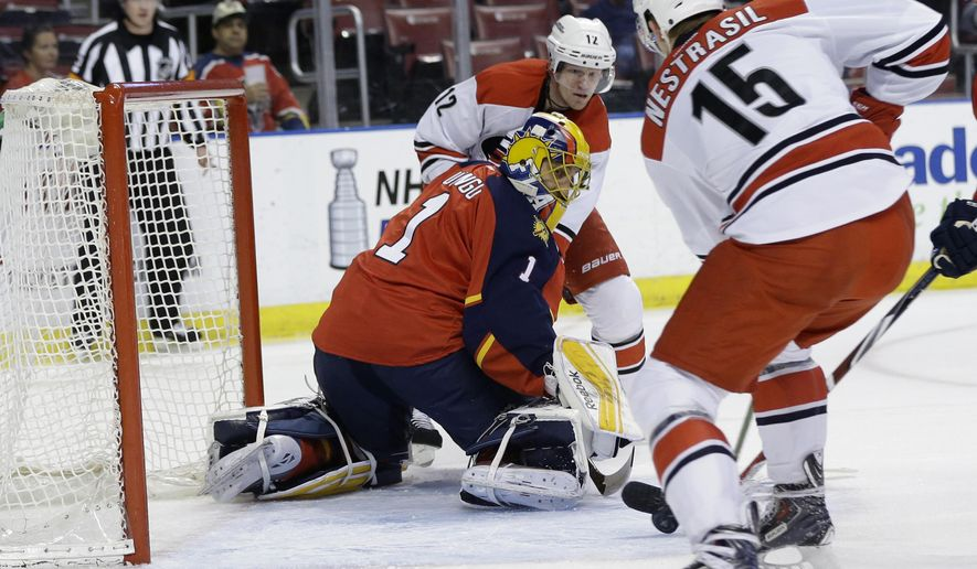 Carolina Hurricanes right wing Andrej Nestrasil (15) attempts a shot on the goal as Florida Panthers goalie Roberto Luongo (1) defends during the first period of an NHL hockey game, Thursday, April 2, 2015, in Sunrise, Fla. Also shown is Carolina Hurricanes center Eric Staal (12). (AP Photo/Lynne Sladky)
