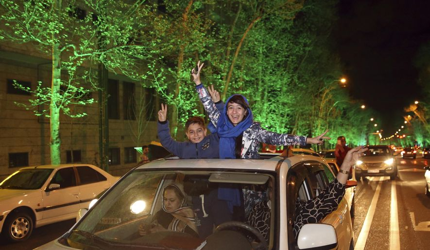 Iranians flash the victory sign from their car while celebrating at a street in northern Tehran, Iran, Thursday, April 2, 2015, after Iran's nuclear agreement with world powers in Lausanne, Switzerland.  The United States, Iran and five other world powers on Thursday announced an understanding outlining limits on Iran's nuclear program so it cannot lead to atomic weapons, directing negotiators toward achieving a comprehensive agreement within three months.(AP Photo/Vahid Salemi)
