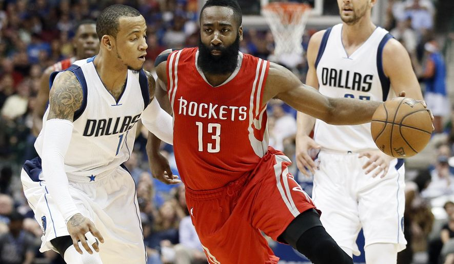 Dallas Mavericks' Monta Ellis (11) defends as Houston Rockets' James Harden (13) drives to the basket for a score in the first half of an NBA basketball game Thursday, April 2, 2015, in Dallas. The Mavericks' Chandler Parsons watches the play from the rear. (AP Photo/Tony Gutierrez)