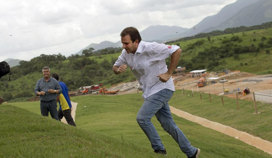 Rio de Janeiro's Mayor Eduardo Paes runs up a hill to speak to journalists after getting a closer look downhill at the ongoing construction of Deodoro Olympic Park in Rio de Janeiro, Brazil, Thursday, April 2, 2015. Deodoro's venues will host some Olympic and Paralympic sports in 2016. (AP Photo/Silvia Izquierdo)