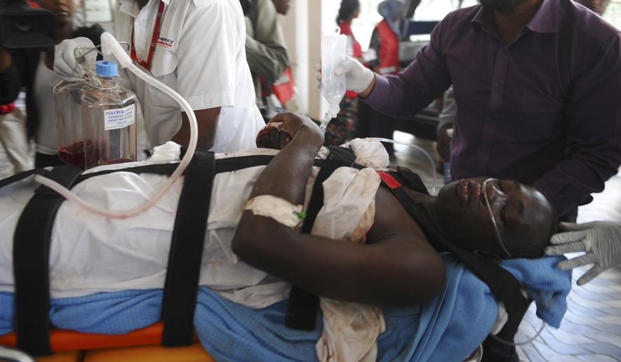 Medics help an injured person at Kenyatta national  Hospital in Nairobi, Kenya, Thursday, April, 2, 2015, after being airlifted from Garissa after an attack by gunmen at Garissa University College in northeastern Kenya on Thursday morning. (AP Photo)
