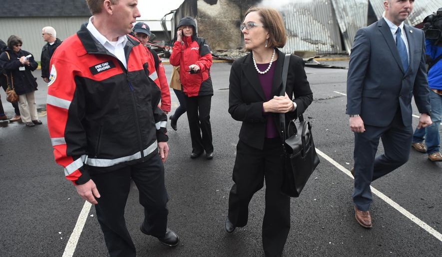 Oregon Gov. Kate Brown talks with Albany Fire Chief John Bradner while touring the scene of a 4-alarm fire that destroyed the South Albany cafeteria, Wednesday, April 1, 2015. (AP Photo/Albany Democrat-Herald, Mark Ylen)