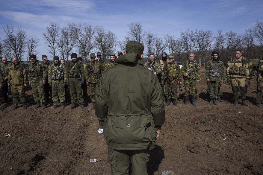 In this Wednesday, March 11, 2015, file photo, pro-Russian rebels line up in front of their commander during a military training exercise near Yenakiyeve, eastern Ukraine. AP reporting, based on dozens of conversations with rebel fighters and visits to their training grounds, has revealed the extent of the involvement of Russian troops in the yearlong conflict. (AP Photo/Mstyslav Chernov, File)