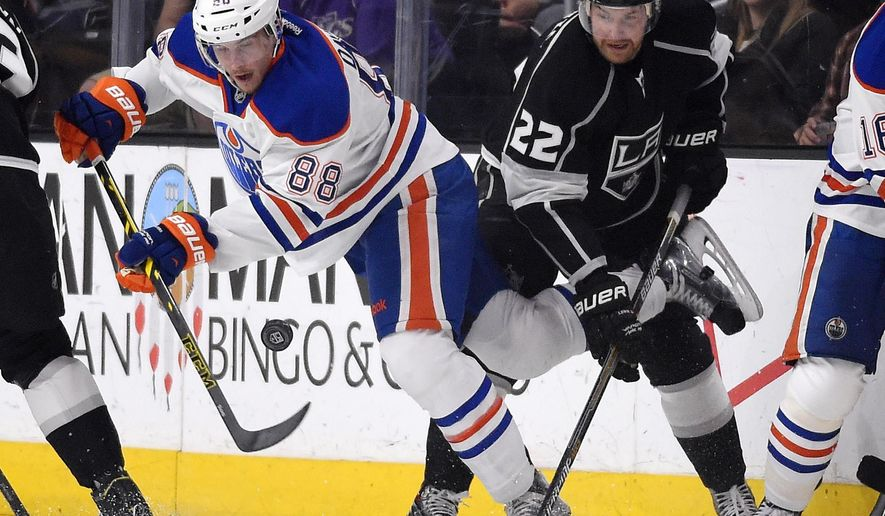 Edmonton Oilers defenseman Brandon Davidson, left, battles with Los Angeles Kings center Trevor Lewis during the first period of an NHL hockey game, Thursday, April 2, 2015, in Los Angeles. (AP Photo/Mark J. Terrill)