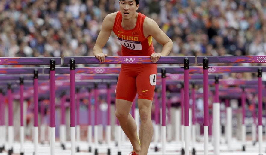 FILE - In this Aug. 7, 2012 file photo, China's Liu Xiang rests on a hurdle after falling in a men's 110-meter hurdles heat during the athletics in the Olympic Stadium at the 2012 Summer Olympics, London.  A Chinese newspaper says the country's former Olympic champion hurdler Liu Xiang plans to announcement his retirement early April, 2015,  following nagging injuries. (AP Photo/Anja Niedringhaus, File)