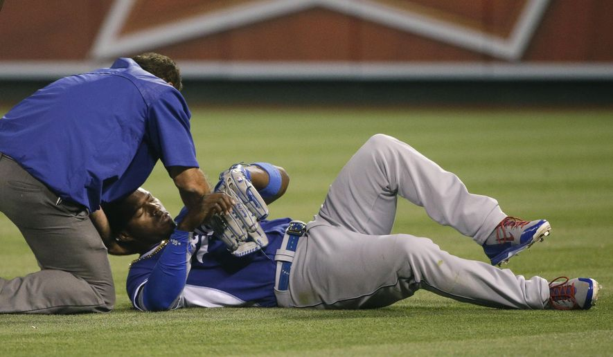Los Angeles Dodgers' Yasiel Puig is tended to by a trainer after he collided with teammate Howie Kendrick during the fifth inning of an exhibition baseball game against the Los Angeles Angels, Thursday, April 2, 2015, in Anaheim, Calif. (AP Photo/Jae C. Hong)