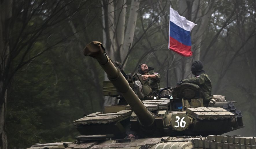 A pro-Russian rebel looks up while riding on a tank flying Russia's flag, on a road east of Donetsk, eastern Ukraine, in this Sunday, July 29, 2015, file photo. (AP Photo/Vadim Ghirda, File)