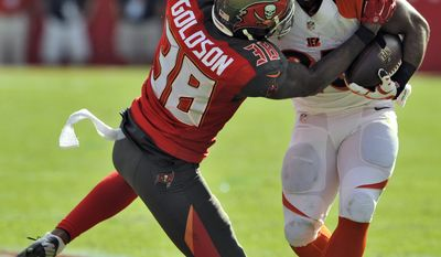 Tampa Bay Buccaneers free safety Dashon Goldson (38) hits Cincinnati Bengals running back Giovani Bernard (25) during the second quarter of an NFL football game Sunday, Nov. 30, 2014, in Tampa, Fla. (AP Photo/Steve Nesius)
