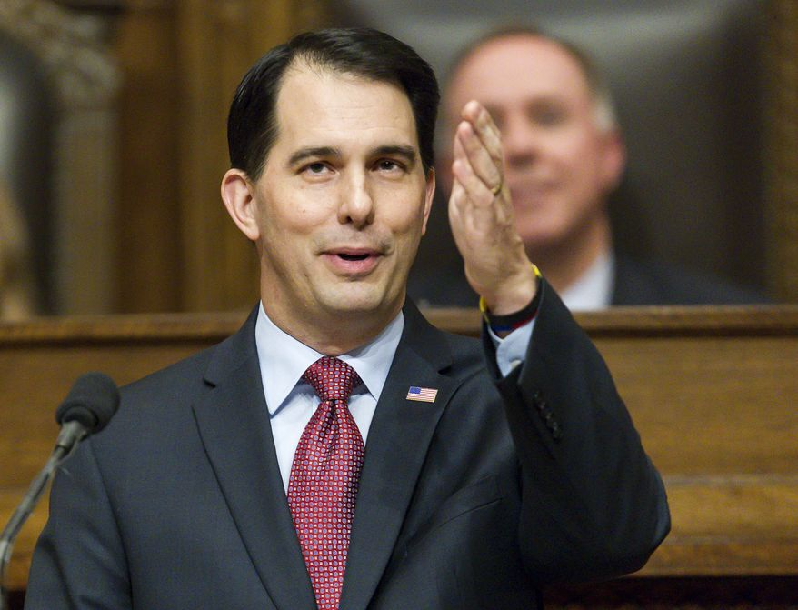 FILE - In this Jan. 13, 2015 file photo, Wisconsin Gov. Scott Walker acknowledges people in the gallery during Governor's State of the State address to a joint session of the Legislature in the Assembly chambers at the state Capitol in Madison, Wis. Walker has transformed Wisconsin politics, winning three elections in four years and signing laws that weaken unions, crippling a key component of the Democratic Party. But the likely Republican presidential contender has had less success changing Wisconsin's economy and budget. The state lags in job growth and its budget faces a shortfall. It's a record that complicates Walker's path in early primary states as he sells himself as a reformer. (AP Photo/Andy Manis, File)