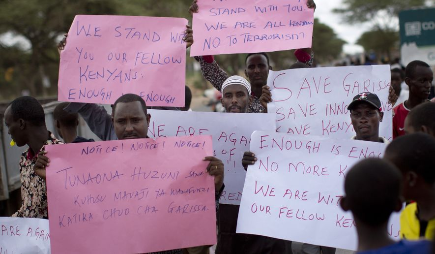 """Kenyan Muslims demonstrate against the attack and in solidarity with those Christians targeted in the attack, on a street in Garissa, Kenya, Friday, April 3, 2015. The Islamic extremists who slaughtered 147 people at the college in northeast Kenya as they shouted """"God is great"""" appeared to have planned extensively, even targeting a site where Christians had gone to pray, survivors said Friday. Sign on left in Swahili reads """"We are very sorrowful, because of the killings of the students, at the school at Garissa"""". (AP Photo/Ben Curtis)"""