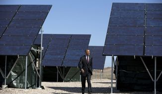 President Barack Obama walks through a solar array at Hill Air Force Base, Utah, Friday, April 3, 2015, to speak about clean energy and the jobs numbers. (AP Photo/Carolyn Kaster)