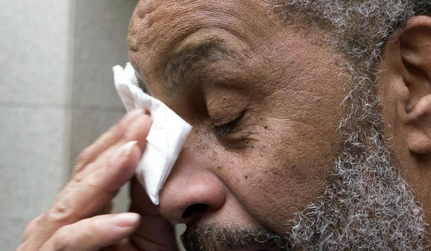 Anthony Ray Hinton wipes away tears after greeting friends and relatives upon leaving the Jefferson County jail, Friday, April 3, 2015, in Birmingham, Ala. Hinton spent nearly 30 years on Alabama's death row, and was set free Friday after prosecutors told a judge they won't re-try him for the 1985 slayings of two fast-food managers. (AP Photo/ Hal Yeager)