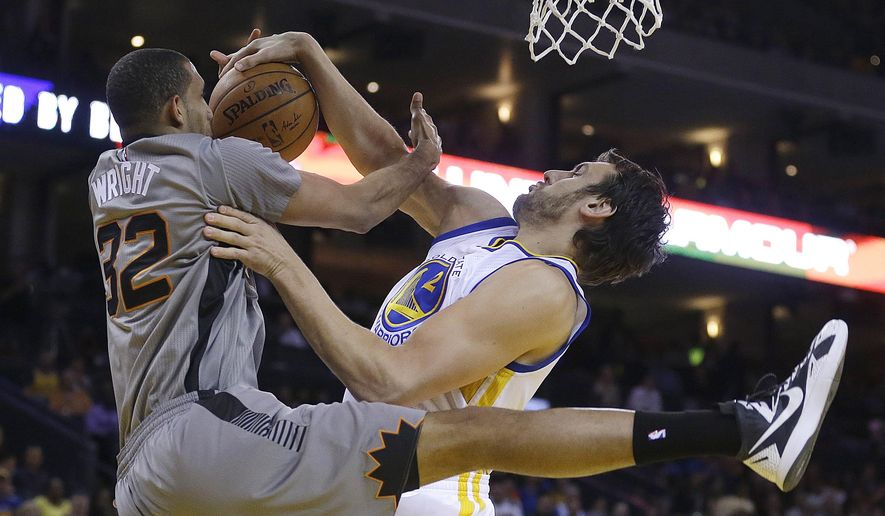 Phoenix Suns' Brandan Wright, left, has his shot blocked by Golden State Warriors' Andrew Bogut during the first half of an NBA basketball game Thursday, April 2, 2015, in Oakland, Calif. (AP Photo/Ben Margot)