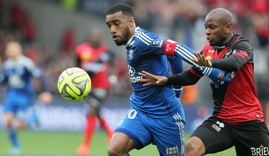 Lyon's Alexandre Lacazette, left, challenges for the ball with Guingamp's defender Baissama Sankoh, right, during their French League One soccer match, in Guingamp, westernFrance, Saturday, April 4, 2015. Lyon won 3-1. (AP Photo/David Vincent)