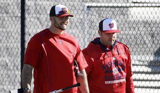 Washington Nationals' Clint Robinson, left, and bullpen catcher Sam Palace walk to the batting cages during an informal spring training baseball workout, Thursday, Feb. 19, 2015, in Viera, Fla. (AP Photo/David Goldman)