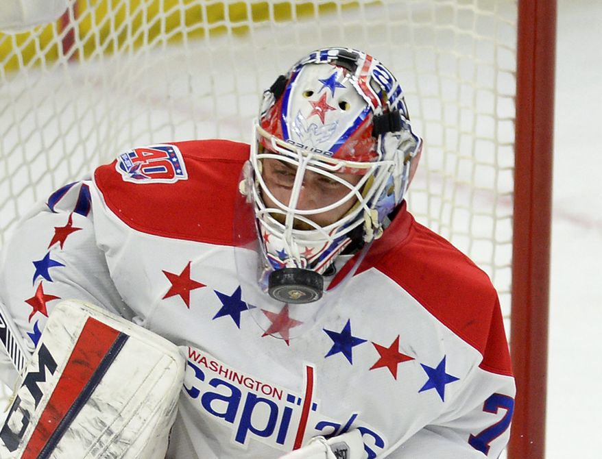 Washington Capitals goaltender Braden Holtby (70) blocks a puck with his mask against the Ottawa Senators during first period NHL action in Ottawa, Ontario, on Saturday April 4, 2015. (AP Photo/The Canadian Press, Justin Tang)