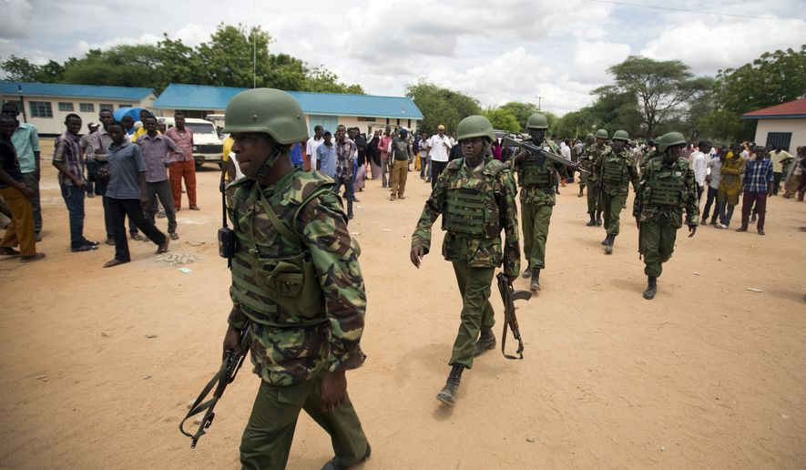 Kenya Defence Forces (KDF) soldiers arrive at a hospital to escort the bodies of the attackers to be put on public view, in Garissa, Kenya Saturday, April 4, 2015. Authorities displayed the bodies of the alleged attackers involved in the killings at Garissa University College on the bed of a pickup truck that drove slowly past the crowd gathered in a large open area. (AP Photo/Ben Curtis)