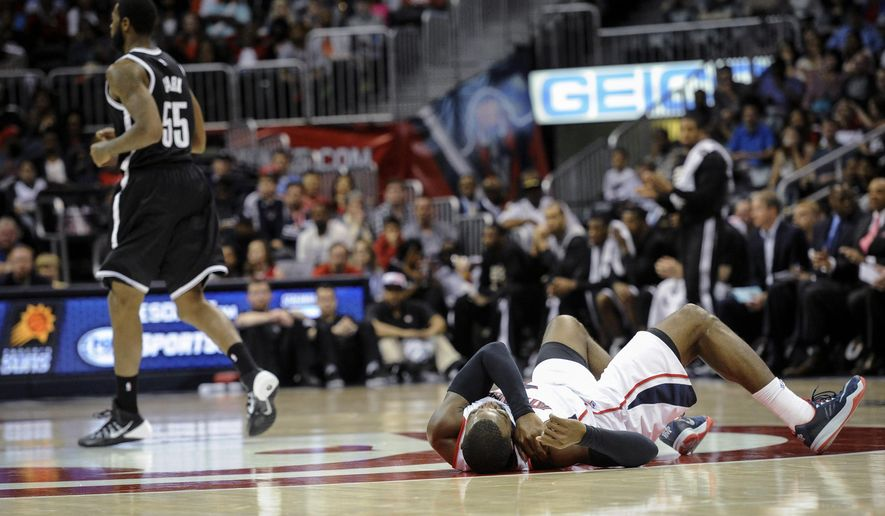 Atlanta Hawks forward Paul Millsap, lies on the floor after injuring his shoulder against the Brooklyn Nets during the first half of an NBA basketball game, Saturday, April 4, 2015, in Atlanta. Millsap went to the bench and later left the game. (AP Photo/John Amis)