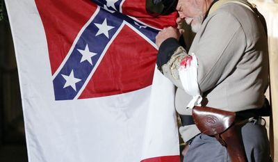"""In this March 27, 2015 photograph, """"Daddy,"""" played by Kearby Swofford, portraying a Confederate major, cries as he prepares to lower the wartime flag following his return from the war during a scene in the Historic Natchez Tableaux, performed in Natchez, Miss. Author Greg Iles helped rewrite the tableaux this year, a long-time tradition presented during the Spring Pilgrimages of historic houses, to include scenes featuring African-Americans, lessening the traditional glorification of the Old South. (AP Photo/Rogelio V. Solis)"""