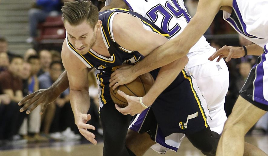 Utah Jazz forward Gordon Hayward, left, is fouled by Sacramento Kings forward Carl Landry, center, as he tried to drive between Landry and Kings forward Omri Casspi, of Israel, right, during the first quarter of an NBA basketball game in Sacramento, Calif., Sunday, April 5, 2015.(AP Photo/Rich Pedroncelli)