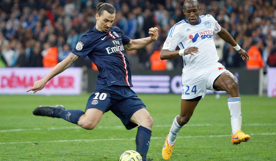 Paris Saint Germain's Swedish forward Zlatan Ibrahimovic, left, challenges for the ball with Marseille's French defender Rod Fanni during the League One soccer match between Marseille and Paris Saint-Germain, at the Velodrome Stadium, in Marseille, southern France, Sunday, April 5, 2015. (AP Photo/Claude Paris)