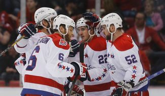 Washington Capitals' Mike Green (52) celebrates his goal against the Detroit Red Wings with teammates in the second period of an NHL hockey game in Detroit, Sunday, April 5, 2015. (AP Photo/Paul Sancya)