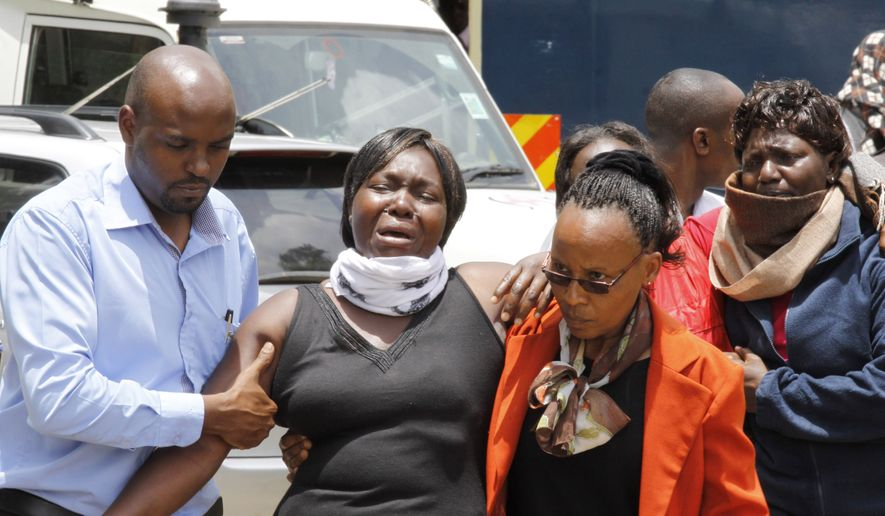 A woman is helped after she viewed the body of a relative killed in Thursday's attack at Garissa university in northeastern Kenya, at the Chiromo funeral home, in Nairobi, Kenya, Sunday, April 5, 2015. (AP Photo/Khalil Senosi)