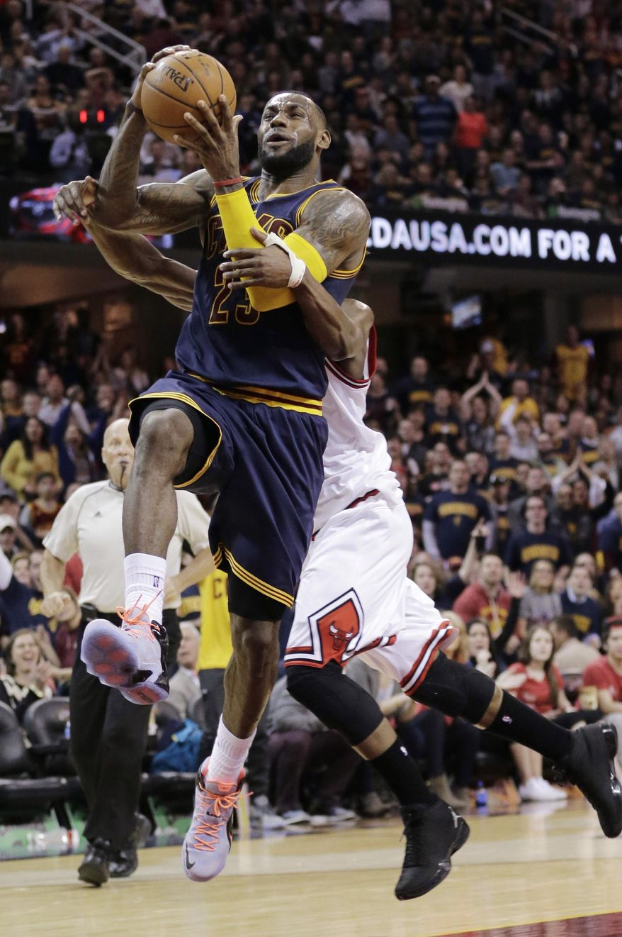 Cleveland Cavaliers' LeBron James, front, is fouled by Chicago Bulls Jimmy Butler during the third quarter of an NBA basketball game Sunday, April 5, 2015, in Cleveland. The Cavaliers defeated the Bulls 99-94. (AP Photo/Tony Dejak)